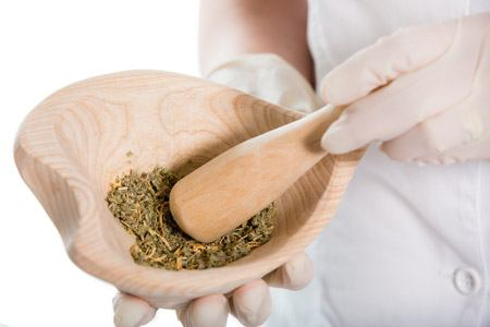 Woman doctor using a mortar and pestle, herbal medicine