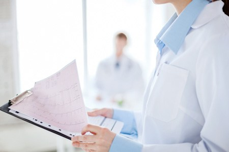 healthcare and medicine concept - close up of female holding clipboard with cardiogram